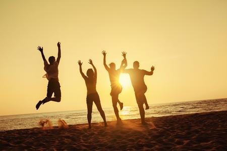 楽しい 4 人の友人のグループ、実行、サンセットビーチにジャンプします。シー trave 休日コンセプト。テキストのためのスペース 写真素材 - 87116368