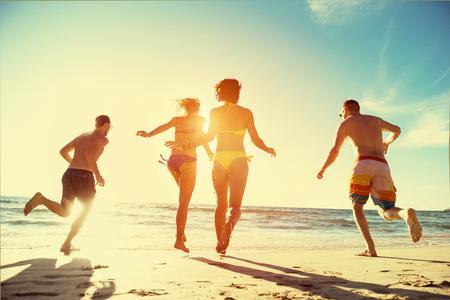 Happy friends run sunset beach holidays