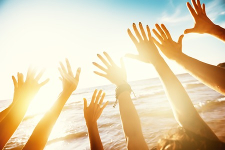 Friends travel concept with hands and sunset sea