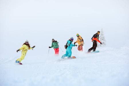幸せなスノーボーダーとスキー場でスキーヤーのグループ 写真素材