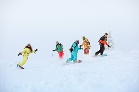 Group of happy snowboarders and skiers on ski slope Stock Photo