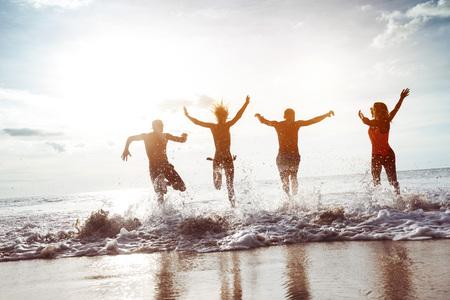 Four happy friends runs to sunset beach Zdjęcie Seryjne