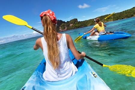 Two ladies at sea kayaks walking in blue lagoon