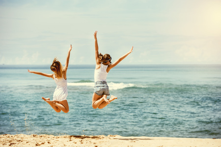 Two happy girls jumps at sunny beach