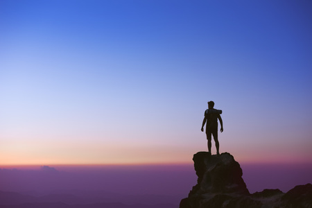 Man's silhouette at mountain top on background of sunset sky 스톡 콘텐츠