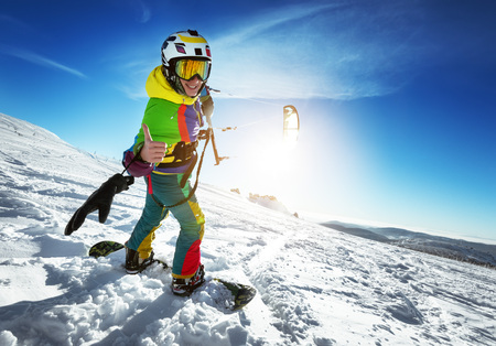 Happy lady snowboarder with snow kite Imagens