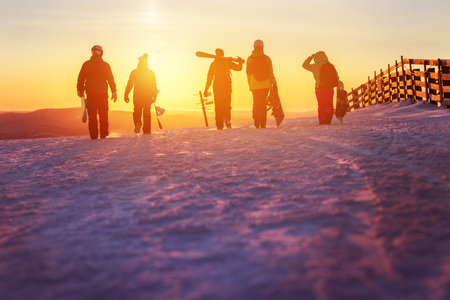 Friends with ski and snowboards walking to sunset