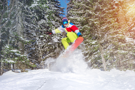 Snowboarder backcountry jump offpiste against frozen forest
