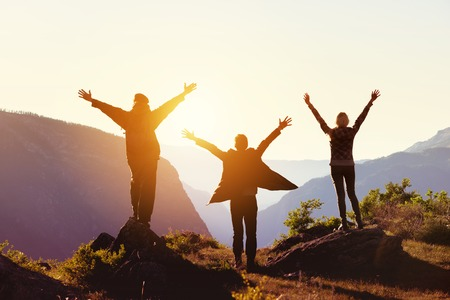 Travel concept with three happy friends against sunset mountains Banco de Imagens