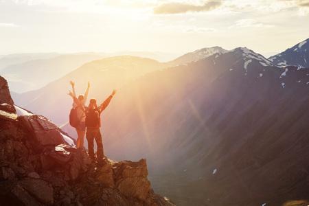 Dwa szczęśliwy turystów pozdrowienia zachód słońca z uniesionymi rękoma Zdjęcie Seryjne