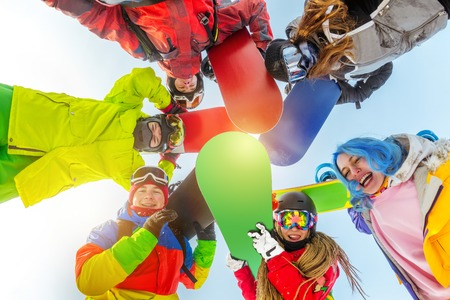 Group of happy friends stands in circle with snowboards