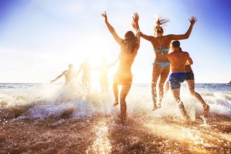 Happy friends at sunset sea beach Banco de Imagens - 96171935