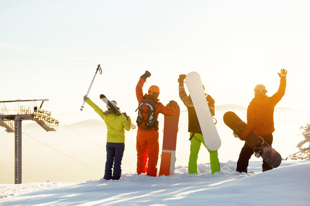 Group of happy skiers and snowboarders having fun