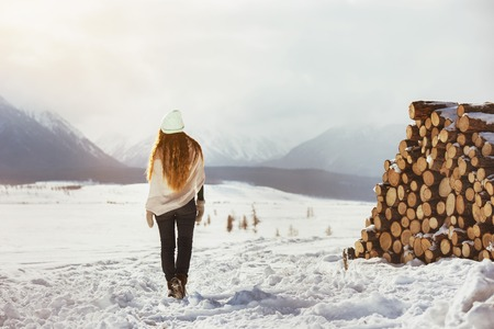 Lady stands against mountains and pile of firewood