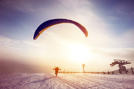 Skydiver runs or starts flight at sunset mountain Stock Photo