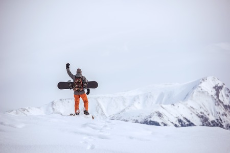 Snowboarder stands on mountain top ski tour concept 写真素材