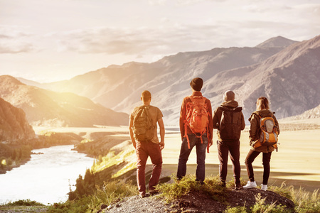 Four friends sunset mountains travel concept