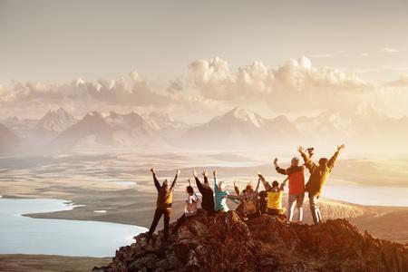 Duża grupa ludzi na szczycie góry sukcesu