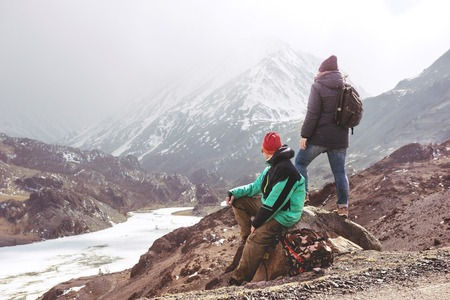 Two tourists at view point against mountains