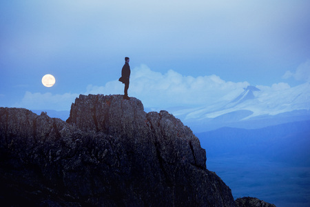 Lonely man at evening stands on cliff against mountains and moon