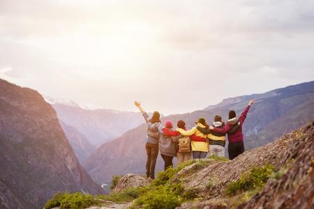 Happy friends cliff against mountains Standard-Bild
