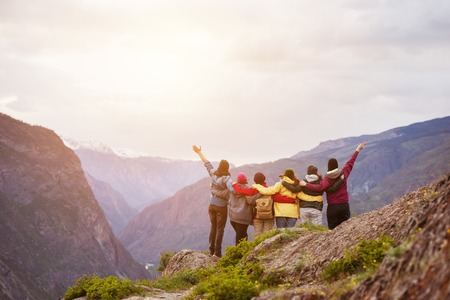 Happy friends cliff against mountains Stock Photo