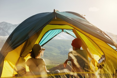 Couple rest in tent against mountains sunset