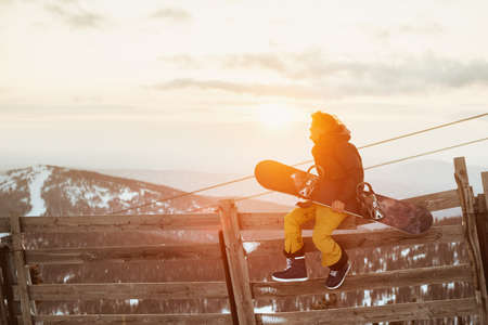 Snowboarder sits on fence with snowboard Stock Photo