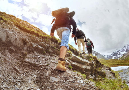 Group of three tourists walking uphill by trek in mountains