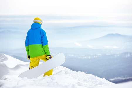 Snowboarder stands with snowboard on top mountain