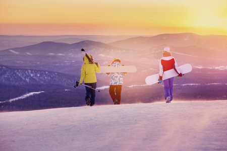 Three friends skiers and snowboarders are walking on mountain top at sunset