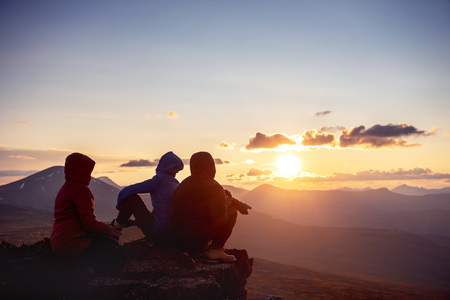 Three friends sits at the rock ang looks at mountains and sunset. Travel or active tourism lifestyle concept