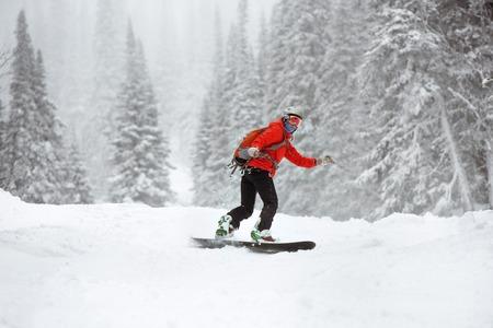 Snowboarder at offpiste slope in forest. Ski resort