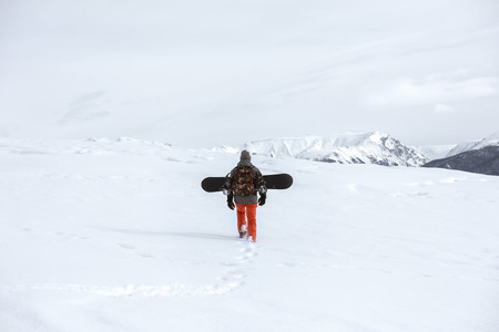 Snowboarder goes uphill at ski tour in mountains