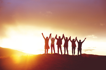 Big group of happy friends with raised hands at sunset. Peoples silhouettes. Unity, success, team or friendship concept Stock Photo