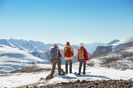 Three tourists stands on the top of mountain pass and looks at view