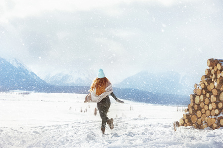 Happy young girl runs at first snow in mountains