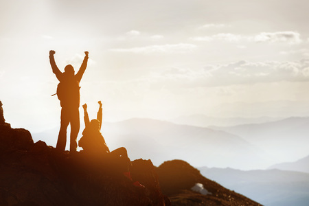 Silhouettes of two happy tourists at mountain top. Success or win concept Stock Photo