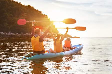 Happy family is walking at sunset sea by kayak or canoe. Active tourism concept Фото со стока