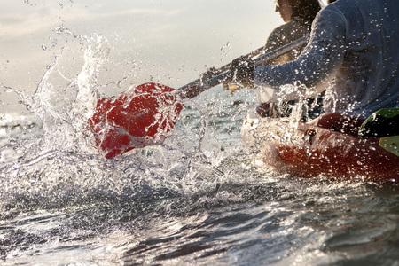 Closeup photo of splashes from kayak or canoe paddle at sea bay. Kayaking or canoeing concept