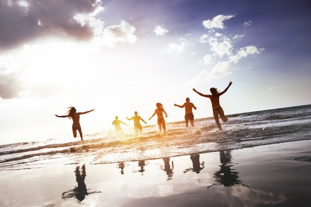 Group of happy peoples runs and jumps at sunset sea beach. Tropical tourism concept Zdjęcie Seryjne