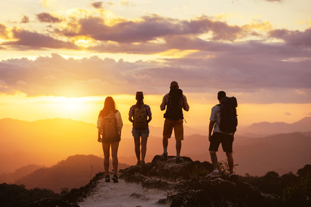 Group of four peopes silhouettes stands on mountain top and looks at sunset