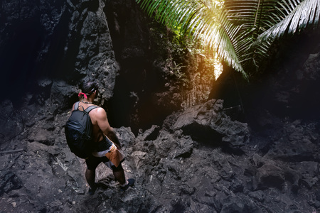 Man climber stands near caves exit or big rock in darkness