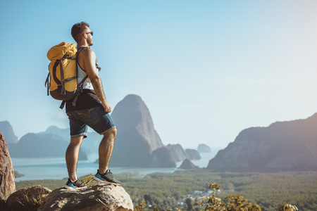 Hiker stands on mountain or viewpoint and looks at view with sea and islands. Travel concept Imagens
