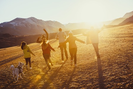 Big group of happy friends run and jump at sunset field against mountains and sun