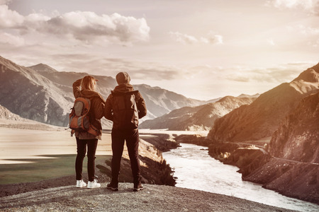 Couple of travelers stands on viewpoint and looks at mountains and river from viewpoint. Travel concept with space for text