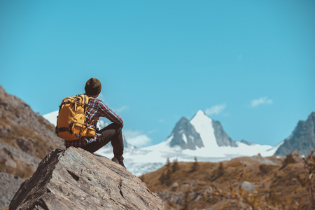 Man hiker with backpack sits on big rock and looks at white mountain with glacier