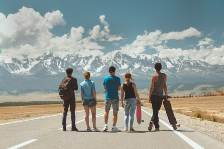 Group of five friends stands on long straight road and looks at mountains. Travel concept 版權商用圖片