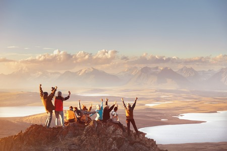 Large group of happy friends is having fun on mountain top and looks at mountains valley. Adventure or travel concept