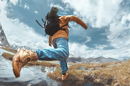Hiker jumps across water in mountains area. Hiking concept with man